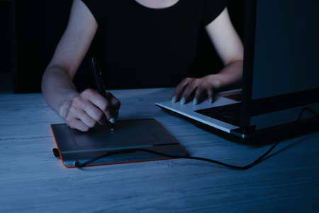 Designer drawing at graphic tablet late at night Stock Photo