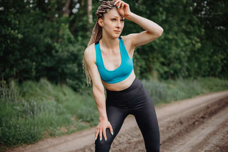 Fit woman wiping sweat after morning jogging