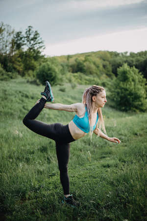 Sporty fit young woman doing yoga in nature Stock Photo