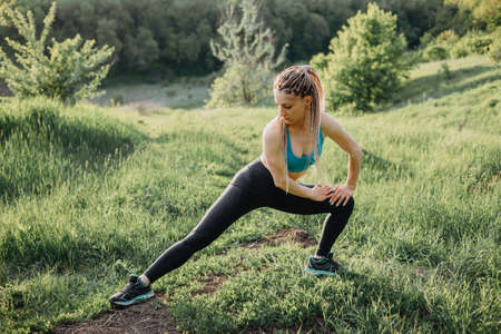 Fit runner does stretching exercise before workout