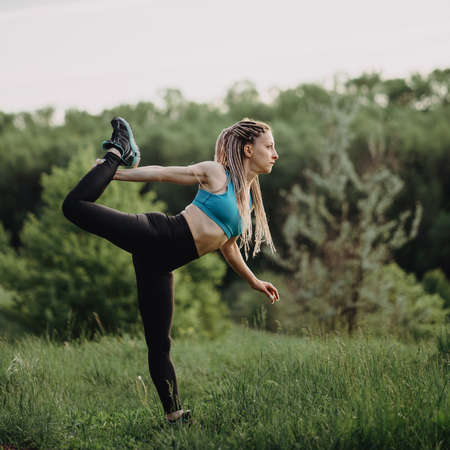 Woman doing stretching exercise, workout in nature