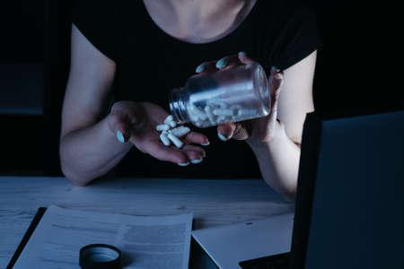 Tired woman taking pills during late night work Stock Photo