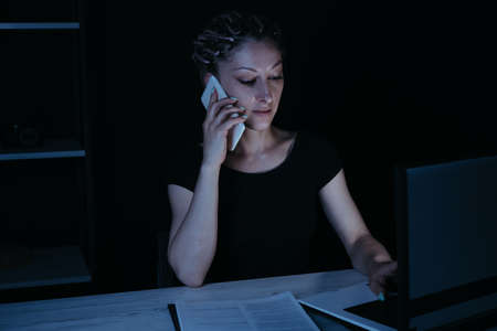 Woman making important call late in the night Stock Photo