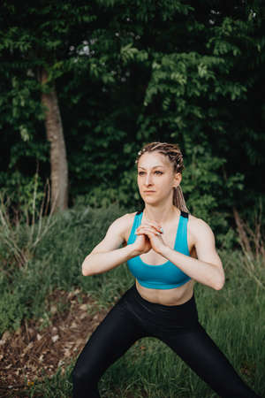 Beautiful sporty woman stretching body in nature Stock Photo