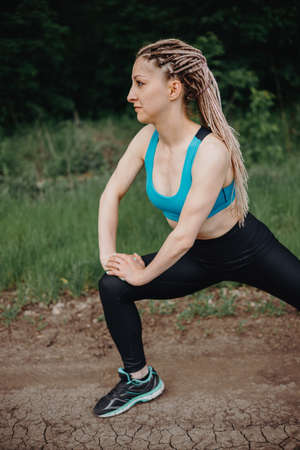 Outdoor sports. Fit woman warming up exercising