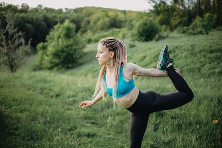 Fit woman runner doing stretching exercise, preparing for morning workout in nature. Outdoor fitness, sport, exercising, people and healthy lifestyle concept.