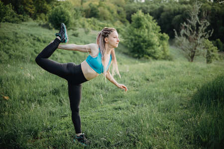 Sporty young woman doing yoga exercises in nature Stock Photo