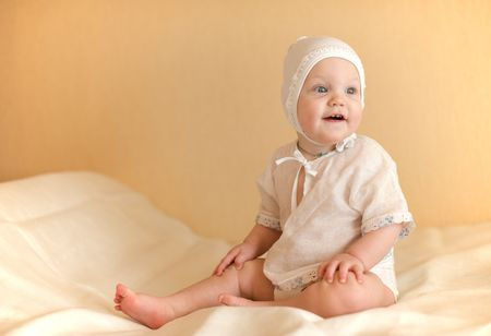 Child dressed in white sits on the bed smiling with his head turned left photo