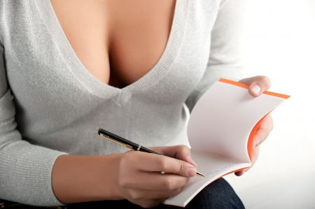 sexy business woman: woman writes in the notebook, which holdes on her knees