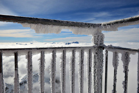 mountaintops: Horizontal landscape of a frost and snow covered balcony in the foreground and a thick layer of clouds and some mountaintops behind it against blue sky. Stock Photo
