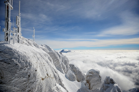 the antennae: Horizontal landscape of a gray, colorless alpine mountaintop with frost covered radio antennae surrounded by a thick layer of clouds against vivid sky.