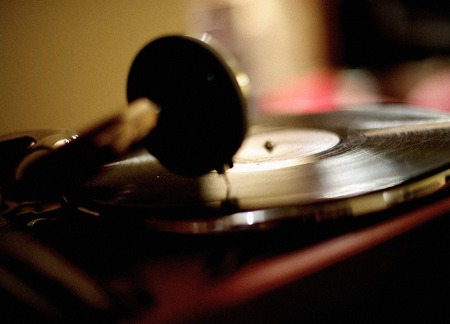 Horizontal shot of the vintage vinyl record player playing scratched LP. photo