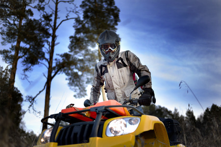 four wheeler: Horizontal close-up of a man in helmet and safety goggles looking into the camera while sitting on quad bike against vivid blue sky. Stock Photo
