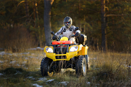 Horizontal portrait of a man in helmet and safety goggles looking into the camera while sitting on all-terrain vehicle against snowy late autumn landscape.