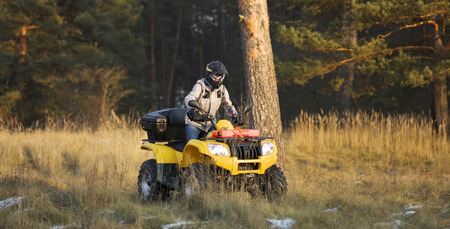 action shot: Horizontal action shot of a man in helmet and safety goggles riding quad bike with snowy autumn forest in the background. Stock Photo