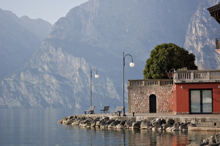 pews: Three pews by the shore of Lake Garda in the northern Italy surrounded by mountains and water.