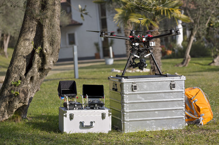 Quadcopter and drone remote controls resting on two aluminum toolboxes against vivid greenery.