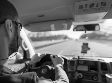 street people: Black and white shot of a man behind the wheel, driving car in a highway. Stock Photo