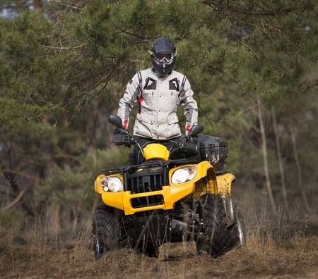 Square portrait of a man in safety helmet and goggles on a yellow ATV 4x4 quad bike in gray sport jacket looking curiously into the camera from behind the pine in the woods. Stock Photo