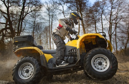 Horizontal motion portrait of a man in gray sport jacket and safety helmet and goggles driving mud-covered yellow ATV 4x4 quad bike with dirt spinning of the wheels.