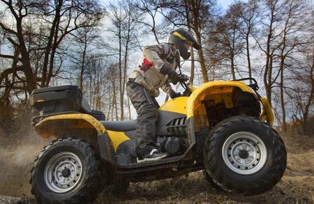 andando en bicicleta: Horizontal retrato de movimiento de un hombre en la chaqueta de deporte gris y casco de seguridad y los anteojos de conducción de barro cubierta amarilla ATV quad 4x4 con tierra giro de las ruedas.