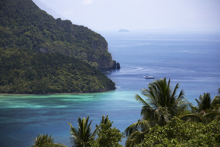 whitehaven: Vibrant seascape of a tree covered tropical coast with luxury yacht sailing into a lagoon.