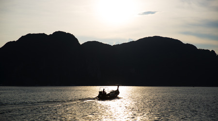 overfishing: Silhouette of an angler on a fishing boat against mountainous coast in the sunset.