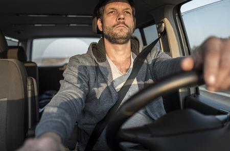 chofer de autobus: hombre sin afeitar cansado está conduciendo el coche