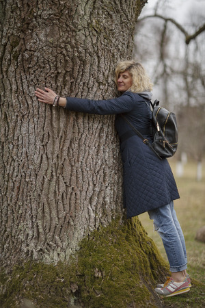 Beautiful blonde girl is hugging tree Stock Photo