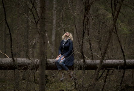 amazing stunning: Girl in wonderland. Blonde girl is seating on the trunk of tree in the deep forest and watching to the sky.