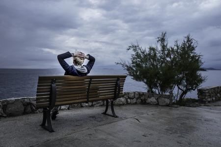 manos levantadas al cielo: La muchacha se est� asentando en el banco cerca del mar y mirando en la distancia