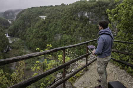 amazing stunning: Man is operating the drone with a Plitvice waterfalls background Stock Photo