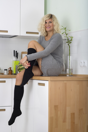 seating: Blonde girl with curly hair is seating on the kitchen table Stock Photo