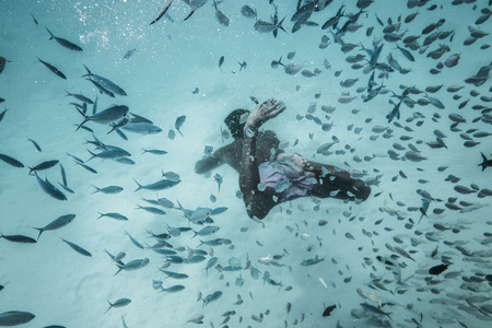 Man is diving among the feeshes in a deep blue water of Indian ocean Stock Photo