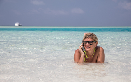 Girl is laying in blue waters of Indian ocean and speaking by telephone