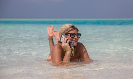 Beautiful smiling girl is laying in blue waters of Indian oceanand speaking by telephone