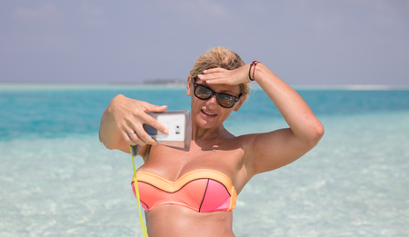 Pretty woman is making selfie on the beach Stock Photo
