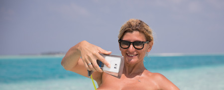 Beautiful smiling girl is making selfie on the beach Stock Photo