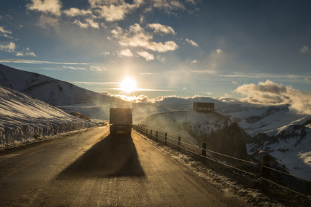 truck on the Caucasus Mountains, Georgian Military road on sunset, winter