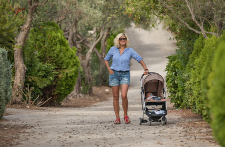 Young beautiful mother with baby stroller smiling to the camera while walking in the green olive park, summer, Greece