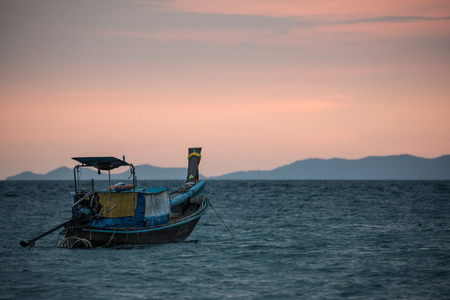 Classic Thailand sunset view with long tail boats, white sand beach, palms, ocean, sun and sky