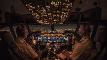 Flight Deck of a modern commercial jet transport aircraft during night cruise. Cozy airliner cockpit atmosphere generated by warm avionic instrument lights and Europe cityscapes in the horizon