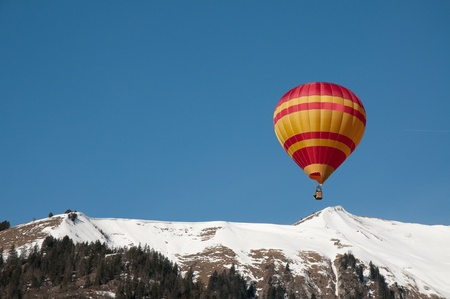 Hotair Balloon over mountains in Chateaux dOex, Switzerland photo