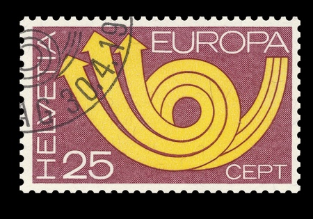 helvetia: Swiss post CEPT stamp showing a symbolic yellow post horn on red ground. (European Conference on post and telecommunication). Helvetia 25 cents. Isolated on black