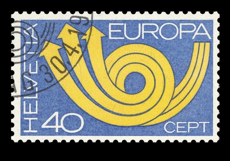 helvetia: Swiss post CEPT stamp showing a symbolic yellow post horn on blue ground. (European Conference on post and telecommunication). Helvetia 40 cents. Isolated on black Stock Photo