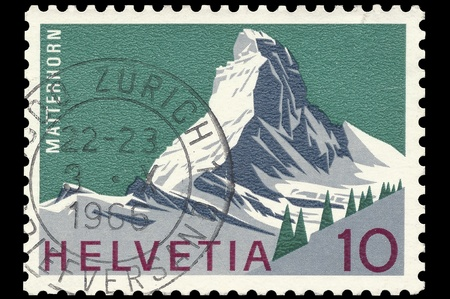 helvetia: Swiss post stamp, with stamp, showing the famous Swiss Matterhorn mountain on green ground. Helvetia 10 cents. Isolated on black Stock Photo