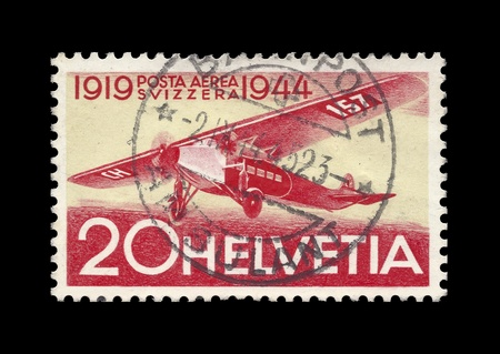25 cents: Swiss post stamp, stamped, showing historic Swissair aircraft in flight. Yellow, red and white colored. Celebrating 25 years of Airmail postal service 1919-1944. Helvetia 20 cents