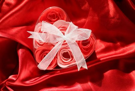 Roses in a box in shape of heart on bright red satin fabric Stock Photo