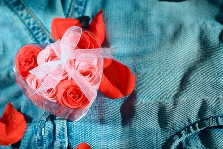 Roses in a gift box in shape of heart on jeans fabric Stock Photo - 4383528