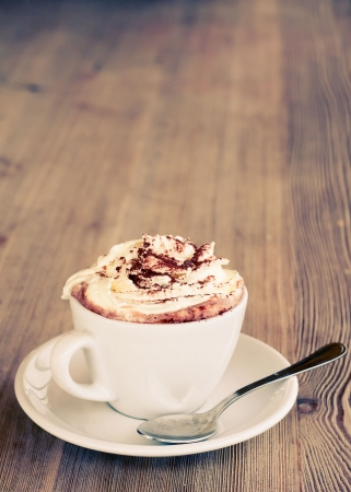 chocolate powder: A cup of hot chocolatewith cream on a wooden textured table Stock Photo